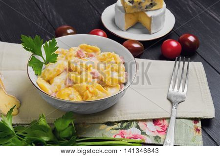 Tortellini with cheese sauce ham ingredients for tortellini cherry tomatoes Camembert cheese blue cheese parsley silver fork on dark black wooden