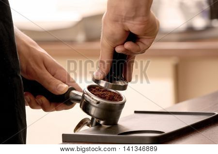 Barista pressing ground coffee with tamper in portafilter