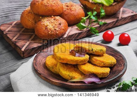Vegetarian food vegetable cutlets for burgers parsley cherry tomatoes lettuce bread buns for burgers wooden dish gray background in rustic style