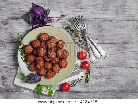 Small meat balls on green plate fresh special spices for meat balls herbs thyme coriander basil rosemary cherry tomatoes silver fork on light white wooden background rustic style top view