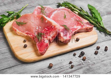 Raw fresh uncooked Pork Meat steak on bone cutting chopping board for cutting raw steaks of pork lettuce and pepper on light white background wooden