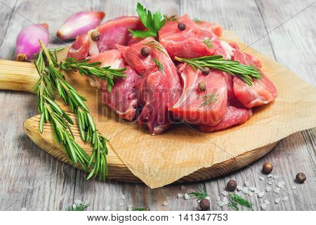 Goulash Pieces of Pork on cutting board on paper for meat goulash rosemary pepper salt shallots on white wooden background