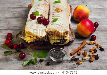 Assortment poppy seed strudel apple and cinnamon strudel cherry strudel cheese raisin strudel fresh cherries apples poppy seeds raisins walnuts lemon balm tray light white wooden background