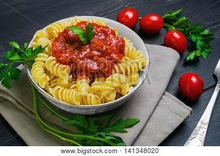 Pasta fusilli with tomato-meat sauce Bolognese ingredients for spiral pasta fusilli cherry tomatoes parsley lettuce white bowl silver fork on black wooden background rustic style