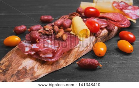 Meat-cutting sausage jerked cheese prosciutto smoked sturgeon nuts almonds pecans cherry tomatoes red yellow on the olive board dark black wooden background