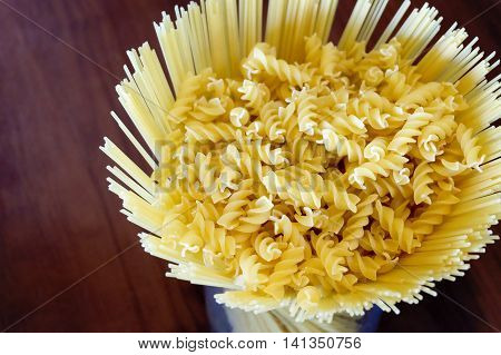 Uncooked pasta spaghetti macaroni Spiral on wooden background