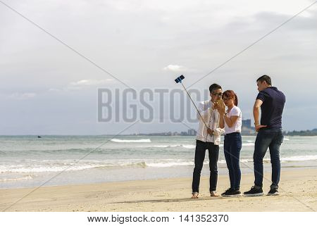 Young People Use Selfie Stick Iat China Beach In Danang