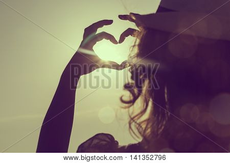 Young woman wearing hat standing on the beach in Syvota bay Greece looking at sunset and making a heart shape with her hands circling the Sun