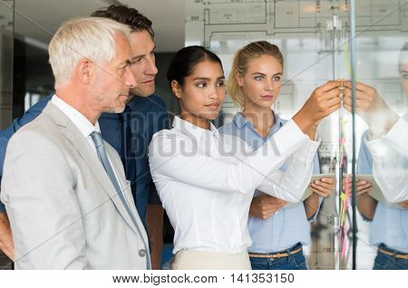 Businesswoman sticking sticky notes on glass wall in office. Multiethnic businesswoman sticking adhesive notes on glass. Colleagues standing in office looking at business woman sticking sticky notes.