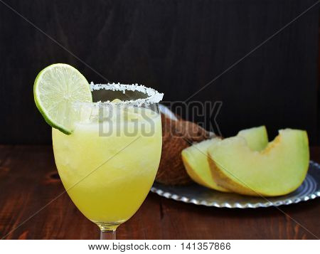 Melon coconut mocktail with lime and ice in glass over wooden table.