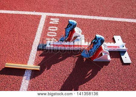 spikes in the starting blocks at the 400m start with a baton