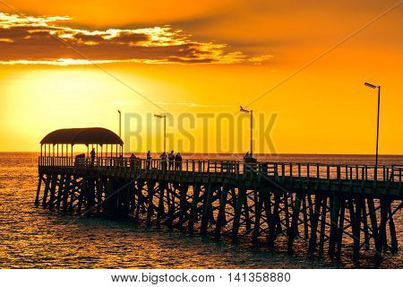 People on Henley Beach Jetty at sunset South Australia. Color-toning applied