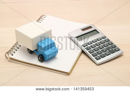 Toy car trucks, a notebook, and a calculator on wood.