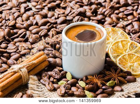 Black coffee in a white cup with cinnamon sticks star anise cardamon and lemon on sackcloth and coffee beans