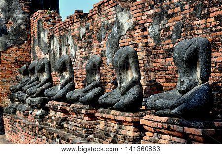 Ayutthaya Thailand - December 21 2010: Blackened remains of a row of stone seated Buddhas lining a walkway between corner chapels at 1629 Wat Chai Wattanaram