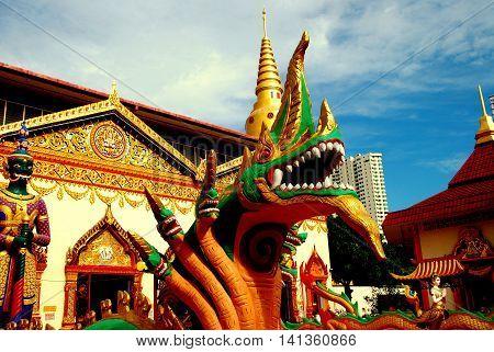 Georgetown Malaysia - January 8 2008: Giant dragon with Naga heads and guardian demon at the entrance to c. 1900 Thai Wat Chaiyamangalaram Buddhist Temple
