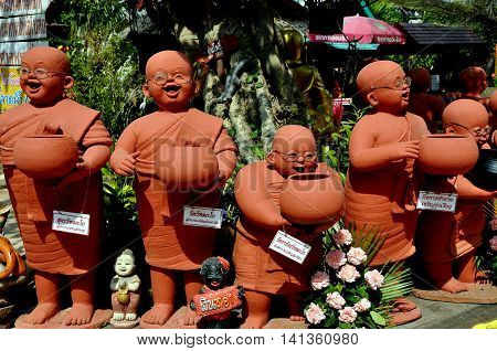Chiang Mai Thailand - December 21 2012: Terra cotta statues of bespectacled monks holding alms bowls abound in the gardens at Wat Tha Ka Rong