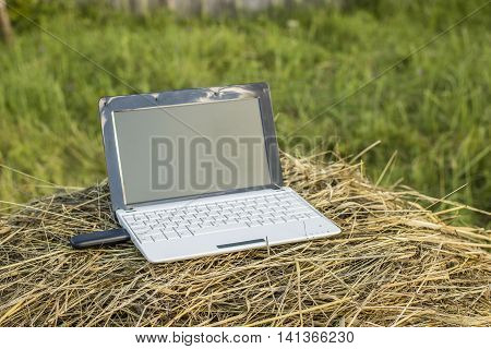 laptop with modem lies on a haystack in a meadow in the village evening at sundown