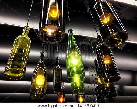 Vilnius, Lithuania - August 4, 2016: Beautiful retro light lamp decor made of empty wine bottles. Toned