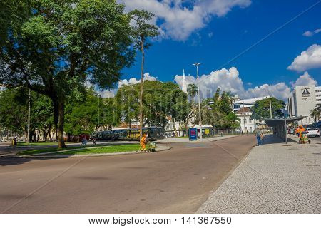 CURITIBA , BRAZIL - MAY 12, 2016: pedestrians walking arround the bus station surrounded by big trees.