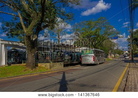 CURITIBA , BRAZIL - MAY 12, 2016: public gray bus picking up passengers from a station, white car waiting for the green light at the corner.