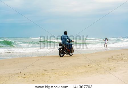 Danang Vietnam - February 20 2016: Man riding the motorbike at the China Beach in Danang in Vietnam. It is also called Non Nuoc Beach. South China Sea on the background.