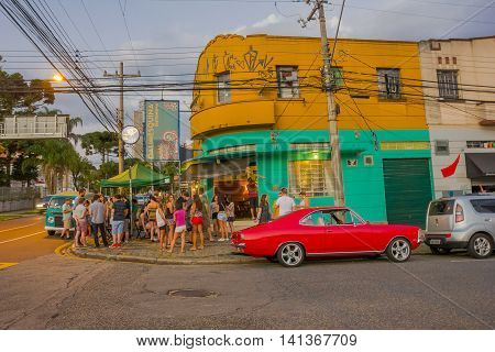 CURITIBA , BRAZIL - MAY 12, 2016: nice red classic car parked at a corner where some people is waiting outside of a restaurant.