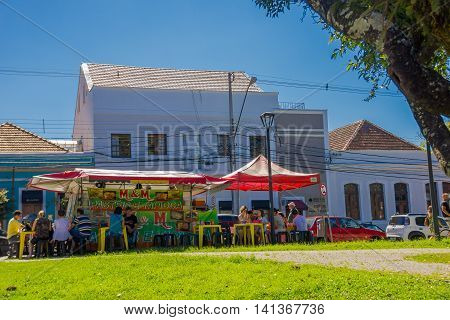 CURITIBA , BRAZIL - MAY 12, 2016: some people eating outside next to a little food stand that offers some traditional brazilian food.