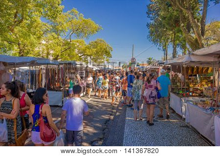 CURITIBA , BRAZIL - MAY 12, 2016: unidentified people visiting the market, lot of stores located at the sides of the street.