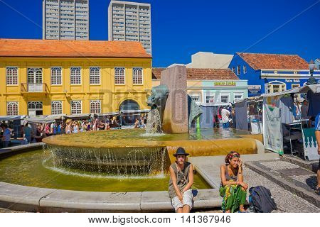 CURITIBA , BRAZIL - MAY 12, 2016: unidentified people sitting in the fountain border, located in the center of the market place.