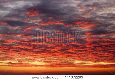 Apocalyptic fiery red and orange sunset sky. Beautiful sky background.