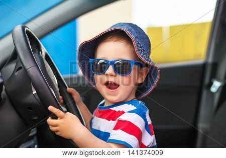 Happy cute little boy with glasses sitting in the car and keeps the wheel