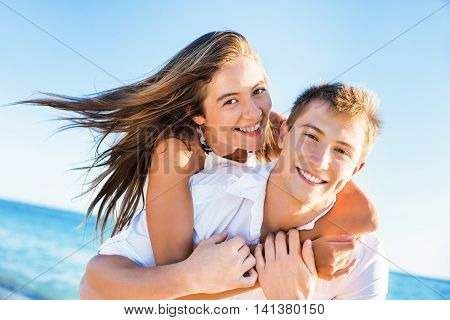 Love - Happy couple on beach having fun piggyback ride outdoor smiling happy laughing together on romantic holidays vacation travel trip. Young multiracial people, Asian woman, Caucasian man, 20s