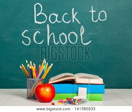 Composition of books, stationery and an apple on the teacher's desk in the background of the blackboard. Back to school