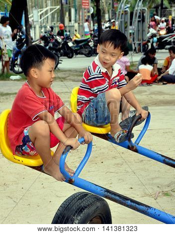 Phuket Thailand - January 7 2011: Two little Thai boys playing on a teeter-totter at Patong Beach playground