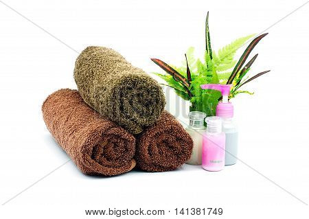 Spa set of Shampoo and Shower gel bottles and brown towel and green leaves in a glass of water on white background.