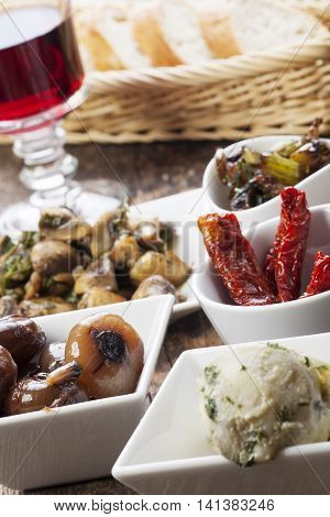 closeup of different italian antipasti and red wine