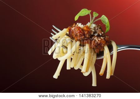 spaghetti with bolognese on a fork on red