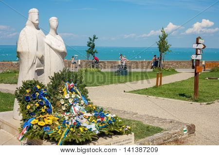 TIHANY HUNGARY - JULY 30 2016: Statue of King Andrew and Anastasia next to the Abbey in Tihany with Lake Balaton in the background.