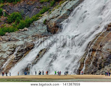 Juneau AK USA - May 25 2016: Visitors watch the majesty of Nugget Falls located adjacent to the Mendenhall Glacier.