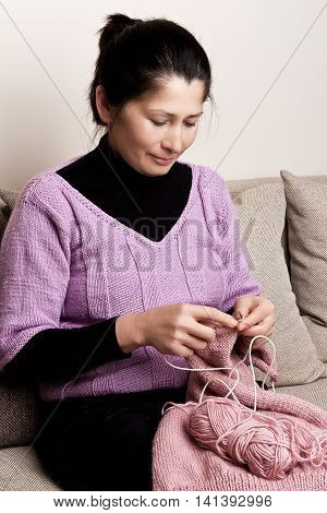 Asian woman knits on spokes a thing, sitting on an sofa in a room