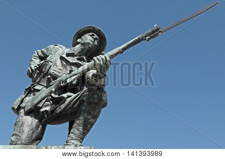 A statue of a British WW1 soldier, wearing a Brody helmet and carrying an SMLE (Lee Enfield) .303 rifle with pattern 1907 bayonet fixed.