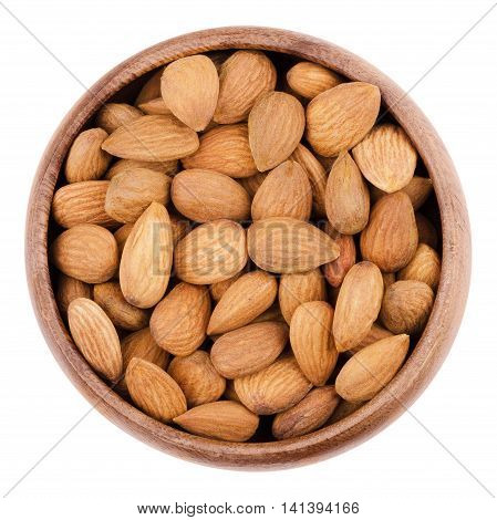 Shelled almonds in a bowl on white background. The raw edible seeds are no nuts, botanically they are drupes. Fruits in a wooden bowl, isolated, macro photo from above. Close up.