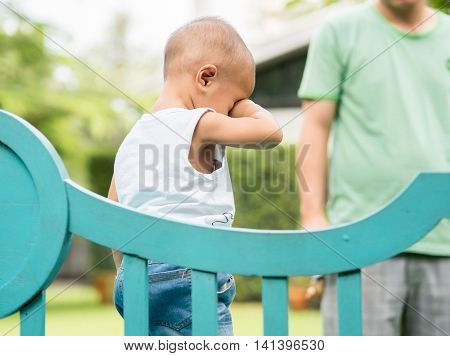 children happily playing on wood bench and crying with his father at green park