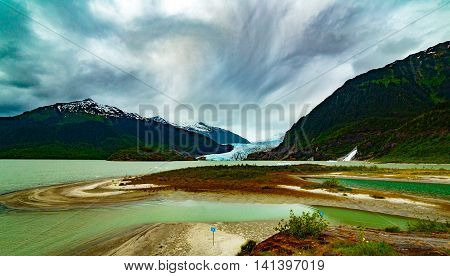: Late afternoon at Mendenhall Glacier in Juneau Alaska in Tongass National Forest. Clouds and peek -a-boo sun provide for dynamic colors and shades in this beautiful spot nearby the Visitor's Center. View of the glacier Mendenh