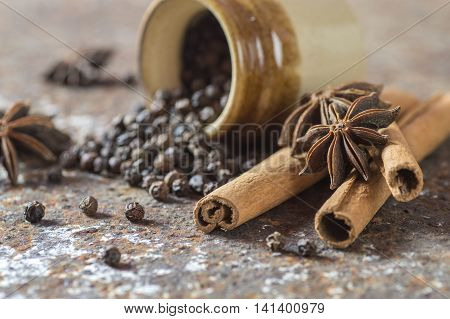 Spices and herbs. Food and cuisine ingredients. Cinnamon sticks, anise stars, black peppercorns on textured background