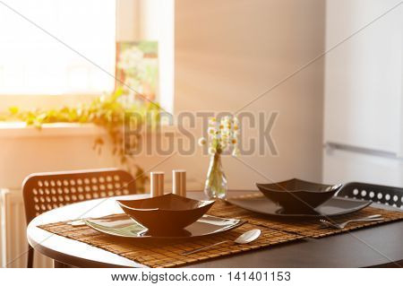 Table served with black dishes on sunny day