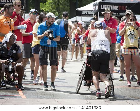 NEW YORK JUL 24 2016: David and Blake Ferrell, father and son, cross the finish line of the NYC Triathlon Race. The run is 10k and the race is the only International Distance triathlon in the city.