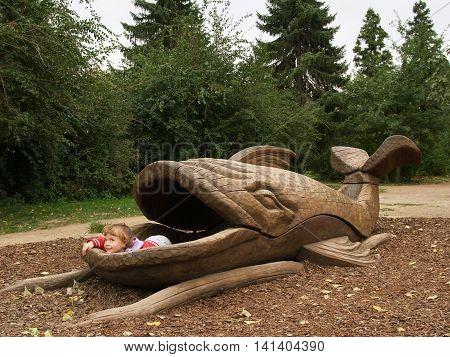 Little girl lying inboard the wooden whale