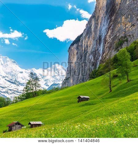 Old chalets on green mountain slope. Swiss Alps. Lauterbrunnen Switzerland Europe.